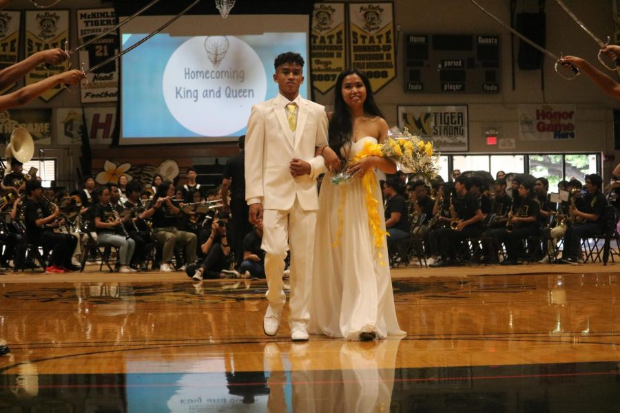 Homecoming King Aaron Velasco and Queen Maya Pegarido walk together as the school cheers.