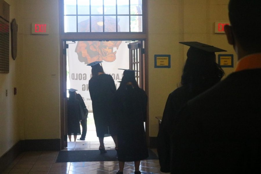 Seniors wait in the lobby of the Administration Building for their turn to turn their tassel and cross the oval.