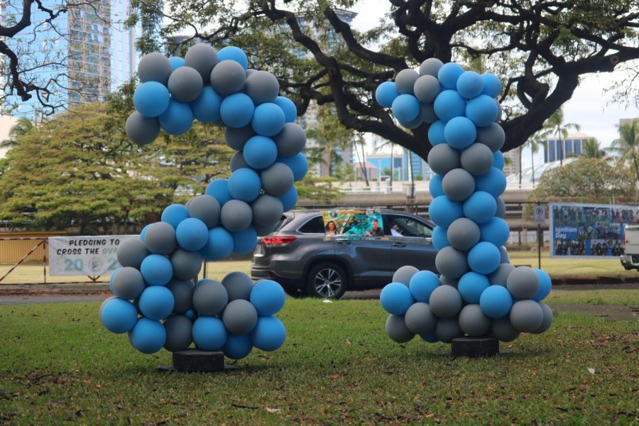 Graduates and their families pass by blue and gray balloons shaped like the number twenty-one as they continue along the route to get to their graduation ceremony.