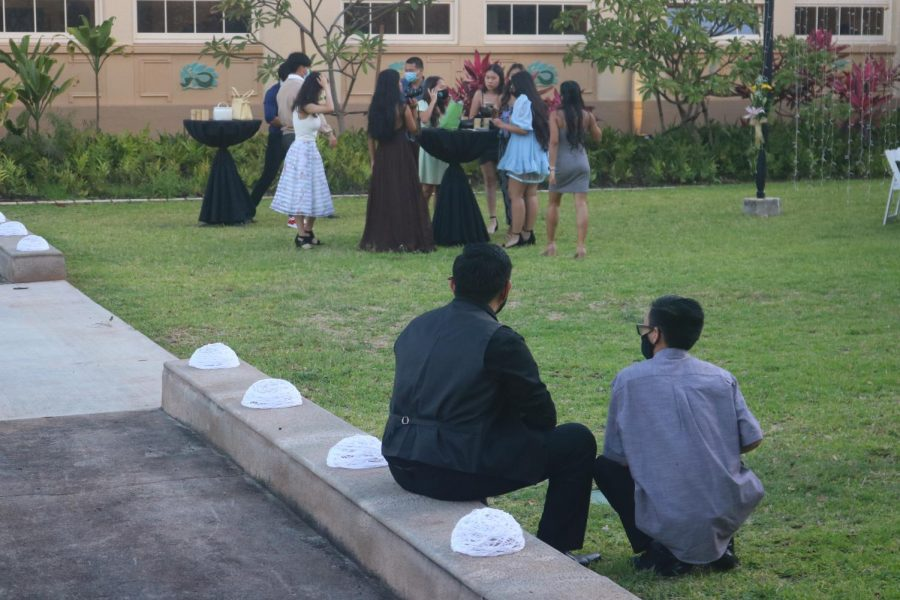 Seniors relax and talk with each other after the dance portion of the first round while larger groups of students swarm a lounge table across the grass.